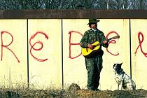 REBEL hraje na kytaru u svého hradu – stavební buňky poblíž hřbitova.
