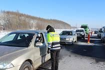 Policisté kontrolují řidiče na D6 za obcí Hory.