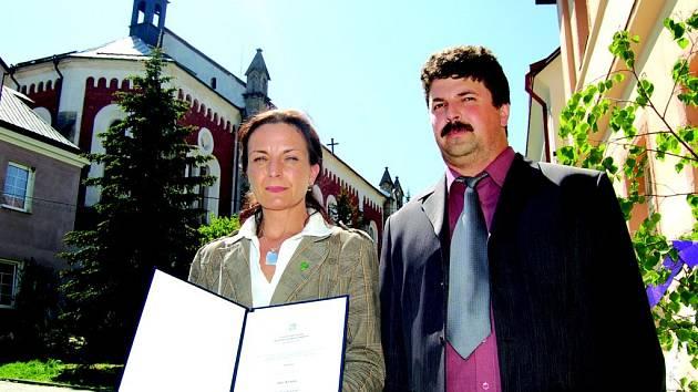 Starostka Lenka Sidorjaková a místostarosta Jan Masopust ukazují dekret, který vrací Krásnu statut města.