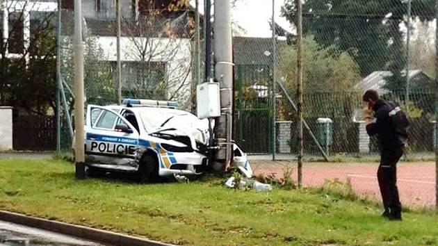 Policejní auto k nehodě nedojelo, skončilo zdemolované ve sloupu.