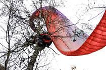 Muž nezvládl přistání a zůstal viset na stromě.