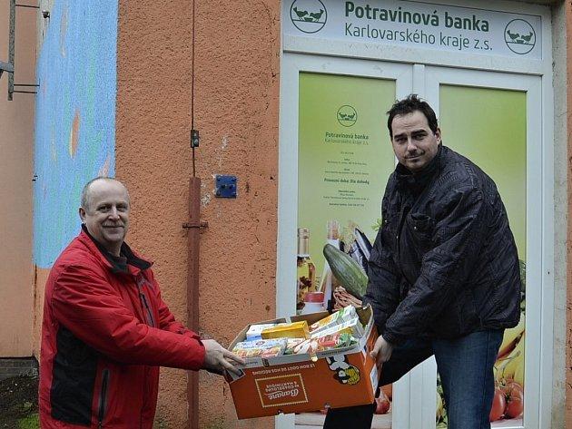 Ředitel potravinové banky Milan Hloušek (vpravo) vydává ze skladu potraviny Liboru Račkovi, vedoucímu Pečovatelské služby v Kynšperku nad Ohří