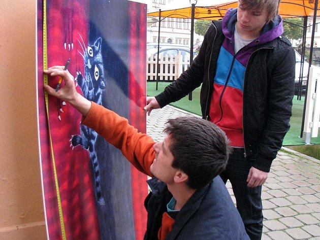 Některé malby z loňského mezinárodního workshopu Plenér Loket dostaly netradiční využití – zaplnily prázdná okna vybraných domů v centru města.