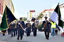 Pochod horníků. Role vlajkonošů se ujali policisté, za nimi hornická dechová kapela