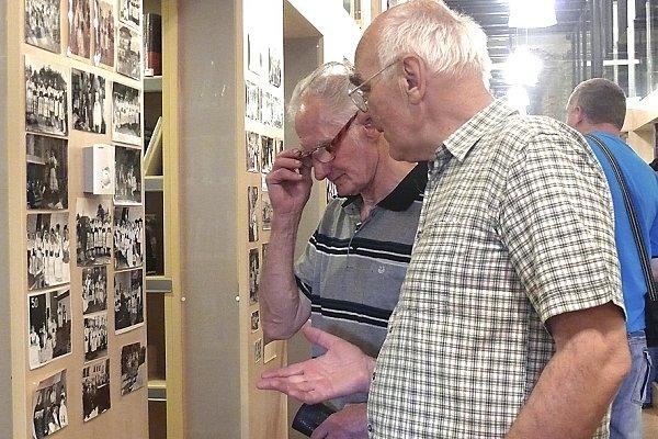 Vojtěch Trubač a Ladislav Bleha (zleva) si prohlíží historické fotografie, na nichž  poznávají své známé.