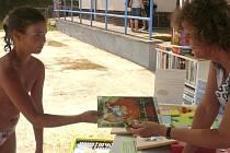 ČTENÍ U VODY. Devítiletá Tereza Dolejší z Prahy má ráda dobrodružné příběhy. Její volba proto včera u bazénu padla na komiks Asterix a velká zámořská plavba. S výběrem jí pomohla  knihovnice Dana Denišová.