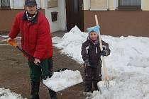 S odklízením sněhu nemají plné ruce práce jen silničáři, ale i obyvatelé měst a obcí se starají o chodníky před domy. Práce se stává nemilou rutinou, zatímco děti si ji užívají.