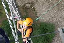 Při lanových aktivitách na Vávrovce jistí žáci jeden druhého.