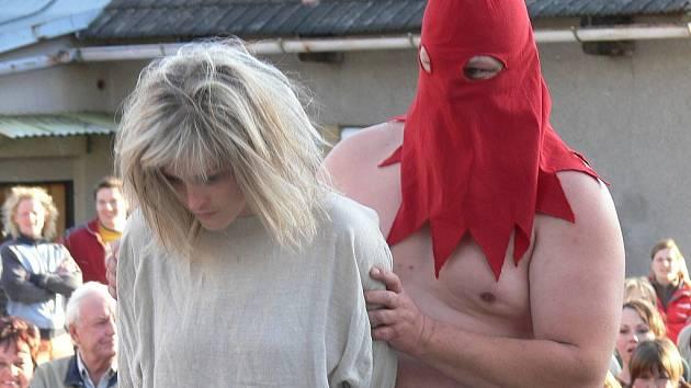 Kat přivádí dívku k pranýři za údajné čarodějnictví
