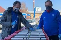 Členové realizačního týmu FC MAS Táborsko pomáhají dezinfikovat košíky a roznášet seniorům nákupy.