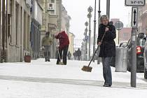 STÁLE AKTUÁLNÍ. Košťata nebo hrabla se stále nevyplatí uklízet. Obchodníci včera opět odklízeli sníh z hlavní ulice 9. května v Táboře.