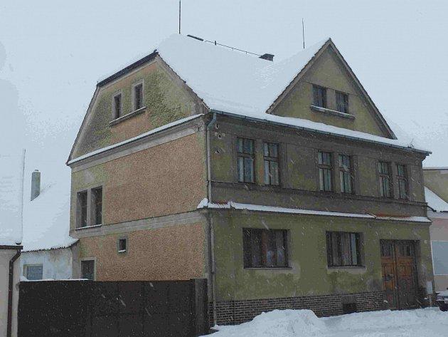 Zimní fotografie domu na náměstí v Malšicích. V přízemí býval obchod.