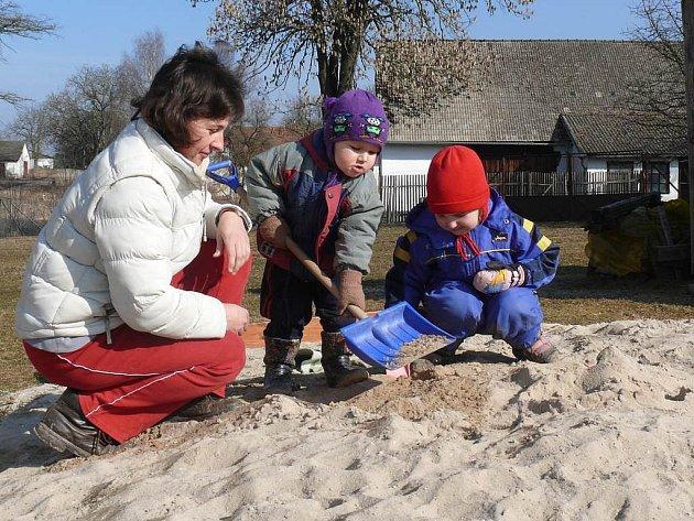 Mladá maminka neodolala pozvání svých dětí Adélky a Vojty na hromadu písku hned vedle domu. Až je  bábovičky omrzí, na procházky do přírody to mají všehovšudy jen pár metrů.