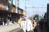 Cestující stojí u přijíždějícího vlaku v bezprostřední blízkosti.