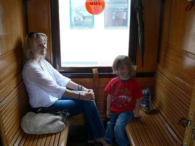 Cestující uvnitř historického vagonu.