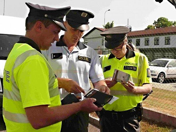 Policisté při prověřování dokladů.