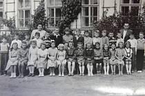 DĚTI PŘED ŠKOLOU. Snímek zachycuje žáky v roce 1958. Jiřího Jecha bychom našli v horní řadě druhého zleva a Jiřího Smolíka ve stejné řadě čtvrtého zprava. Na fotografii jsou kantoři Ludmila Smolíková a řídící Šindelka.