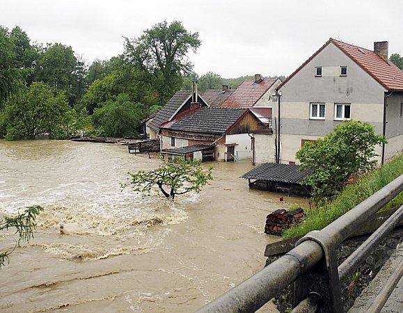 VAL. Hladina Chotovinského potoka se umostu převalila přes kamenný val  a pohltila okolní domy.