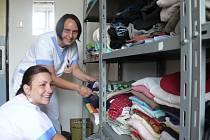 ŠATNÍ BANKA. Sociální pracovnice Věra Prokešová a Daniela Krištofová (vpředu) oblečení v šatní bance pravidelně třídí a obměňují.