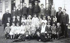 FOTOGRAFOVÁNÍ PŘED ŠKOLOU. Snímek zachycuje společné fotografování ve školním roce 1938 – 1939.  František Zahrádka stojí v druhé řadě vpravo a má bílý límeček.  Na stejné straně je pan učitel František Čížek s brýlemi a vedle něj řídící Haškovec.