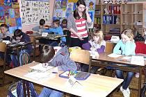 NEZAPOMNĚLY PORADIT. Mladé učitelky obcházely při hodině lavice a nezapomněly také dětem s plněním úkolů poradit. Na snímku Nikola Koubová kontroluje překlad vět.