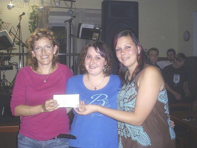 Tři nejdůležitější ženy dobročinného koncertu s obálkou, kde je 11 150 pro postiženou Aniku. Zleva maminka holčičky Ivana Rypáčková, zpěvačka skupiny Pittband Pavla Kafková a Lucie Müllerová, která byla prostředníkem akce.