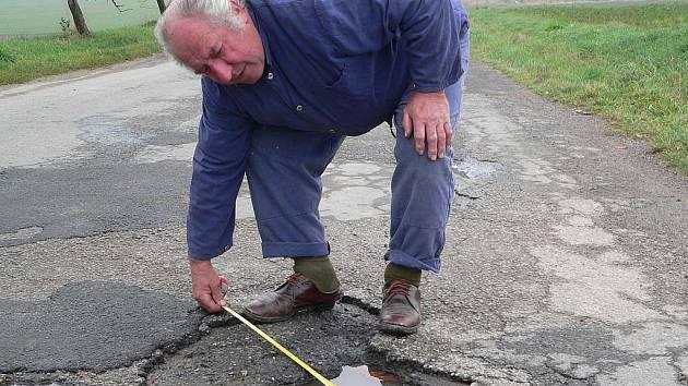VÝMOLY. Jan Šafář z Chrbonína měří díry v silnici III. třídy. Některé jsou i metr široké.