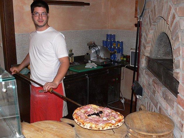 MÁTE CHUŤ? Příprava italského pokrmu v kuchyni táborské pizzerie. Také pizza musí splňovat hmotnostní předpoklady.