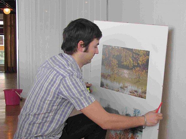 Martin Miler při instalaci fotografií.