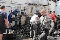 Po požáru motocentra pomáhají kamarádi.