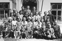 DĚTI PŘED ŠKOLOU. Na snímku vidíme Jaroslavu Krchovou ve školním roce 1955/1956 (ve druhé řadě druhá zleva v bílé halence). Vlevo nahoře je pan učitel Beneš.