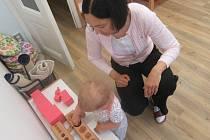 Alexandra Partlová pomáhá Anně Krejčí skládat dřevěné pomůcky podle velikosti.