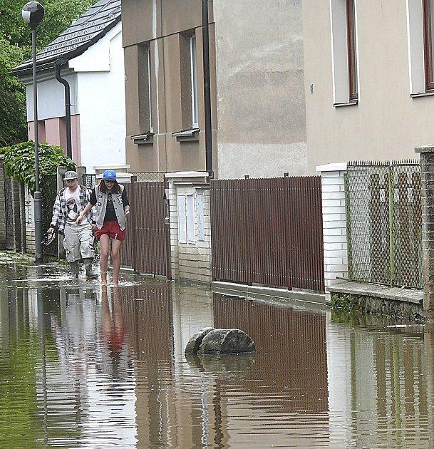 SOKOLSKÁ ULICE. První snímek ukazuje, jak vypadala Sokolská ulice na začátku června 2013, kdy se vní rozlil zjedné strany Bechyňský potok a zdruhé Lužnice.