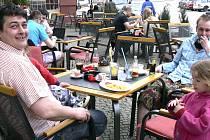 Na táborském Žižkově náměstí návštěvníci jedné z provozoven využili včerejšího slunečného počasí a pozdní oběd si vychutnávali na čerstvém vzduchu.  Jedním z nich byl i Jan Nekovář (vlevo), který od kávy stihl ještě ohlídat okolo pobíhající ratolesti.