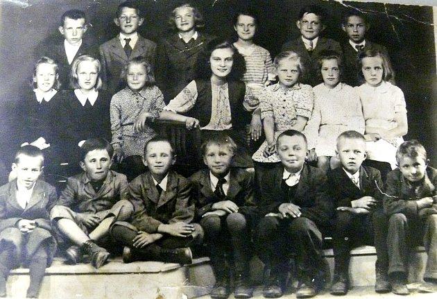 DĚTI Z BRADÁČOVA s paní učitelkou Pokornou asi v roce 1946/7. Milada Jelínková stojí vedle učitelky Pokorné vpravo.