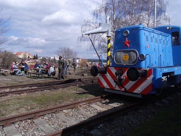 Malá posunovací lokomotiva a účastníci jarního pochodu podél trati při opékání buřtů na bezdružickém nádraží.