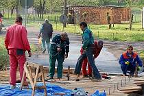 PRÁCE SE CHÝLÍ KE KONCI. Dělníci již pokládají prkna na nově opraveném mostu ve Světcích, práce skončí v neděli.