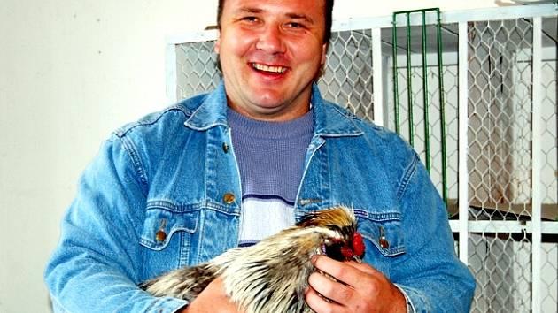Jan Londa drží kohoutka hedvábničky stříbřitošedé.