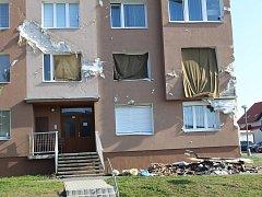Poškozená bytovka měsíc po vichřici.