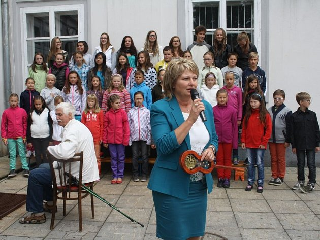 ŘEDITELKA ZUŠ TACHOV Jana Válová se symbolickým klíčem od školy při slavnostním zahájení školního roku. V pozadí Tachovský dětský sbor, který školní rok zahájil.