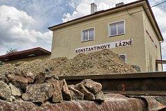 Po kolejích v Konstantinových Lázních jezdí bagr. Železniční zastávka získá nový perón.