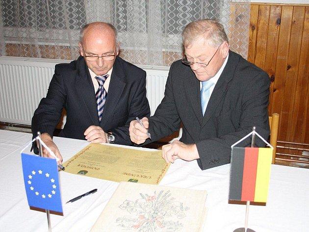 PODEPSÁNO. Starostové František Čurka (vlevo) a Johann Wilhelm (vpravo) právě podepisují dohodu, která poznamená budoucnost Halže i Gutenecku.