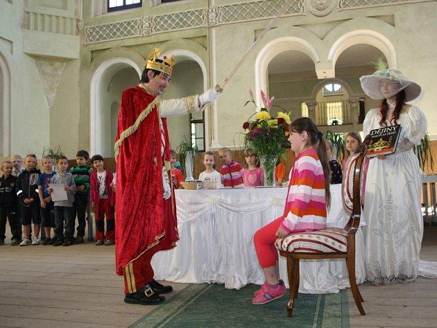 PAVEL VOLTR v kostýmu pohádkového krále právě pasuje Kamilku Havlovou na čtenářku. Kromě ní bylo v pátek pasováno dalších přes osmdesát dětí.