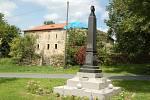 Pomník obětem první světové války v Bernarticích se seznamy padlých ze všech okolních vesnic. V pozadí tvrz, která prochází postupnou rekonstrukcí.