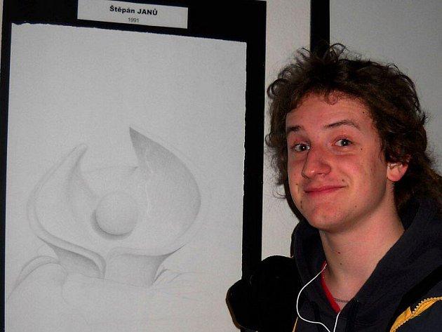Vystavující Štěpán Janů před jednou ze svých kreseb.