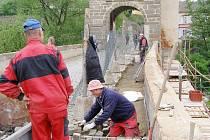 Dělníci davají nový povrch na starý most.