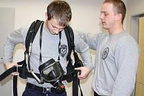 Tachovského hasičského nováčka Lukáše Gesla seznamuje jeho kolega Bohuslav Matoušek s protichemickým oblekem.