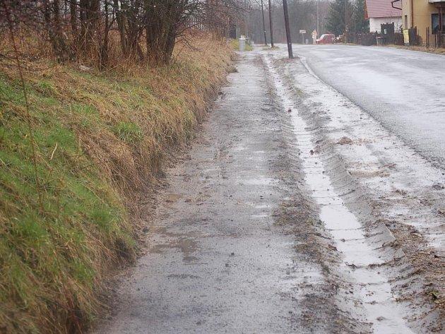 Nová silnice z Tachova do Oldřichova měla být původně letos. Obyvatelése tak letos dočkali alespoň odkrytí části zanešeného chodníku (na snímku).