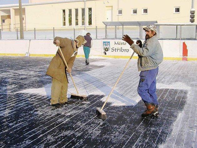 STŘECHA ZATÍM NEBUDE. Provozovatelům stříbrského kluziště tak zatím nezbývá, než si poradit s vrtochy počasí. Snímek zachycuje odklízení sněhu z ledové plochy.