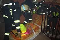 FIGURANTA trvale připoutaného na lůžko přenášejí hasiči na speciální podložce.